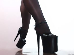 Dominant and strong woman legs with black nylon stockings and tall shoes