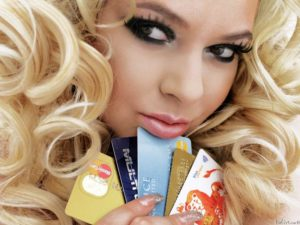 Beautiful blonde girl with credit cards in hands